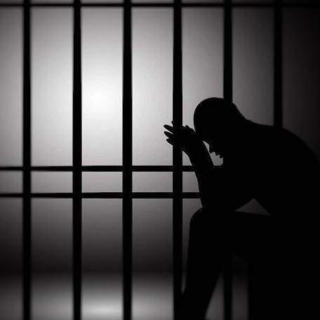A silhouette of a person in a jail cell